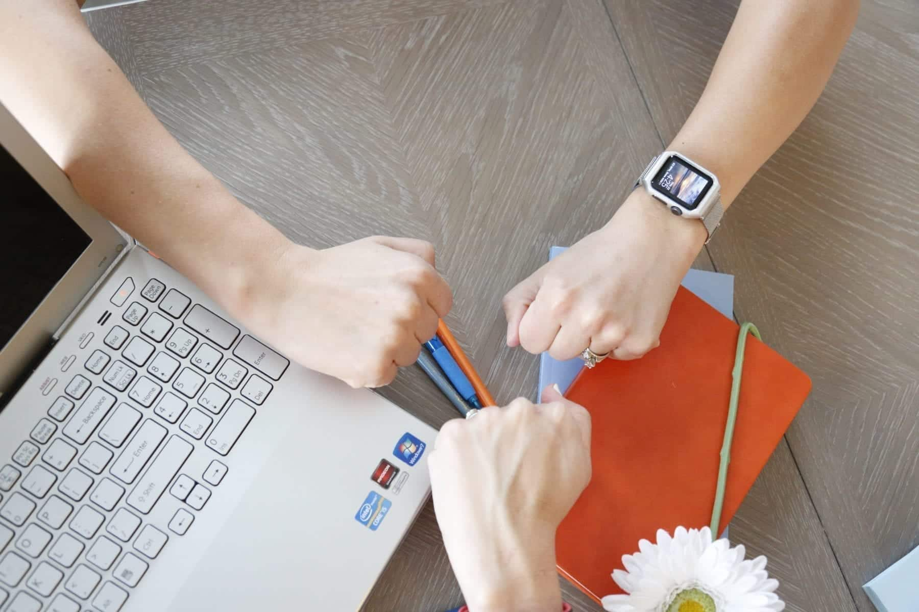 3 women fist bumping over computer and desk celebrating a Facebook marketing win